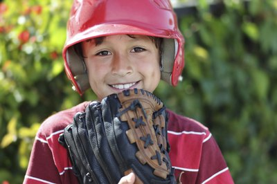 Child in baseball helmet holding up glove