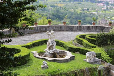 A fountain in the center of a Italian garden.