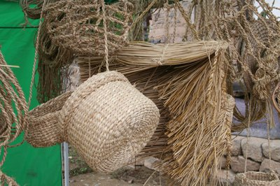 Straw baskets and brooms for sale at a craft fair.