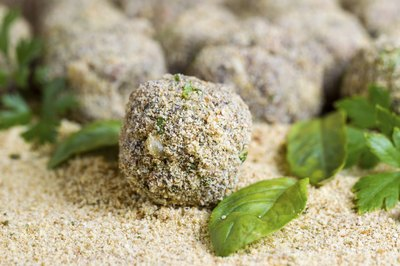 A close-up of ground beef mixed with bread crumbs, herbs and spices and rolled into balls.