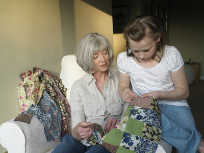 Grandmother and granddaughter looking at quilt