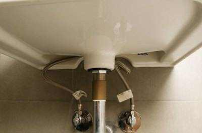 Insert a thin bead of caulk in crevices around pipes under the kitchen sink.