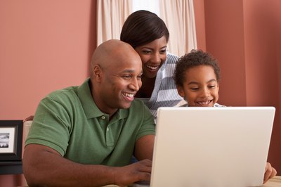 Man looking at laptop with family