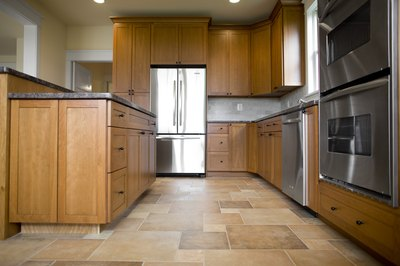 Brown tiles bring out varying shades in oak cabinets.