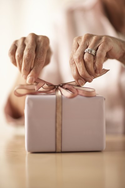 Close-up of woman tying a bow on top of gift.
