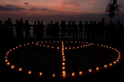 People surround symbol made with candles