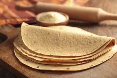 Stack of tortillas on a cutting board.