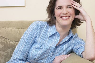 Slightly embarrassed woman looking and smiling on the couch.