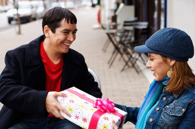 A woman gives a smiling man a present.