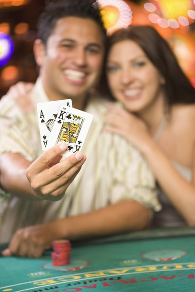 Couple holds up cards and blackjack table