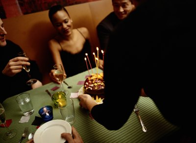 waiter bringing birthday dessert to table