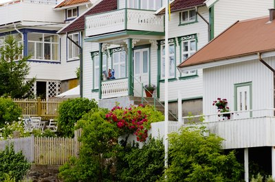 A row of white beach cottages with colorful trim.