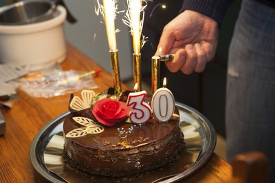 "A chocolate cake with ""30"" candles on top."