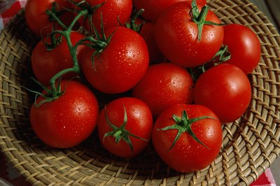 Basket filled with ripe red tomatoes.
