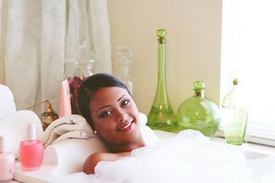 A young woman relaxes in a tub.