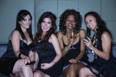 Young women are at a nightclub drinking cocktails.