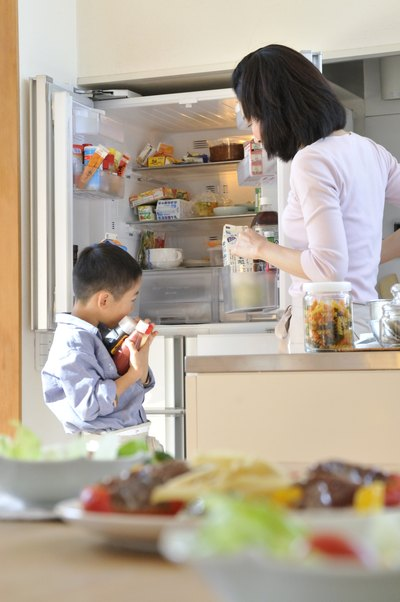 Mother and son putting groceries in fridge