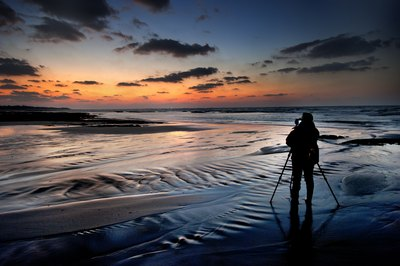 Photographer along shoreline at dusk