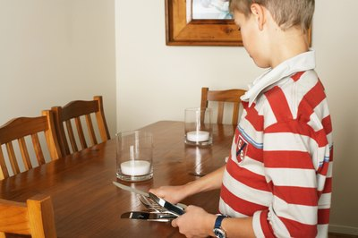 young boy setting table