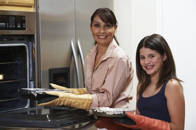 Mother and daughter putting a foil covered dish in oven