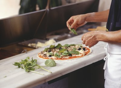 Chef making pizza in restaurant