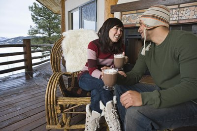 Couple have a hot drink in front of a cabin.