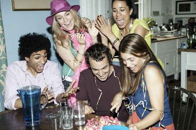 Man cutting birthday cake with friends