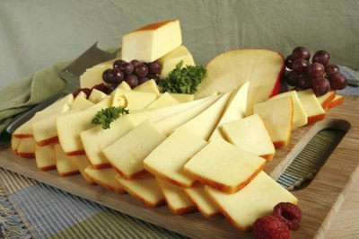 A cheese platter with a few grapes