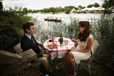 Couple enjoy champagne and smoked salmon lunch by the Henley-on-Thamas river in England