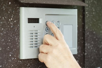 Fingers pushing buttons on an intercom system.
