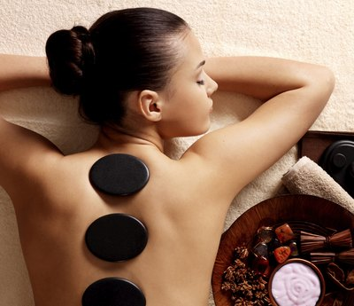 Woman receives stone massage at spa