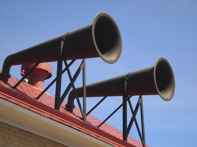 A pair of fog horns on a rooftop.