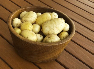 A wooden bowl of golden yukon potatoes on a patio deck.