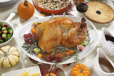 Roast turkey on dinner table with side dishes.
