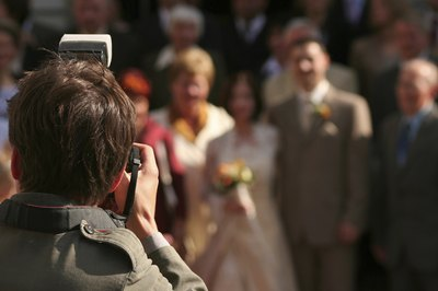 Wedding photographer takes group portrait