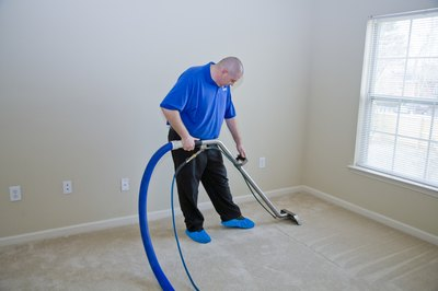 A professional cleans the carpets in a house.
