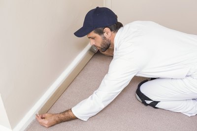 A worker installing wall-to-wall carpeting.