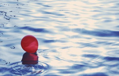A red balloon floating on water.