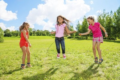 Young children playing jump rope.