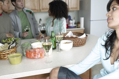 A woman sits at a the kitchen counter at a house party.