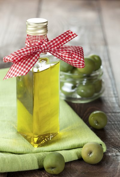 A bottle of olive oil with a gingham ribbon on a rustic table.