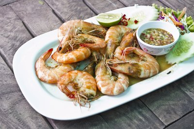 Plate of stewed shrimp on table.