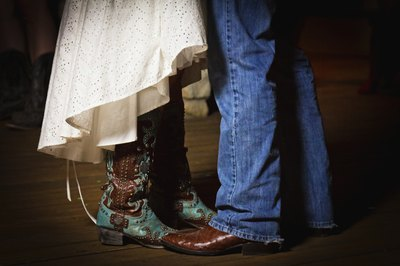 Close-up of man and woman dancing, wearing cowboy boots.