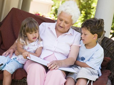 A grandmother looks at a book on the sofa with her two grandchildren.