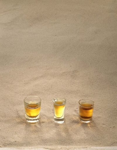 Neat tequila shots on the sand.