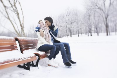 A couple is sitting on a park bench wearing ice skates.
