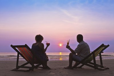Couple sitting together on beach during sunset.