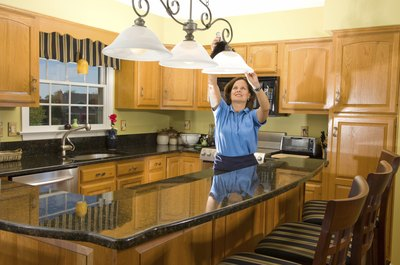 Woman adjusting lamp over granite kitchen top