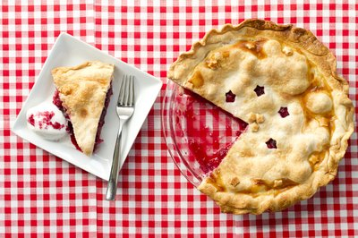 A raspberry pie and single slice on a plate.