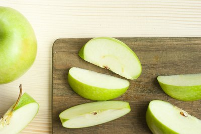 Green apple slices on a wooden cutting board.